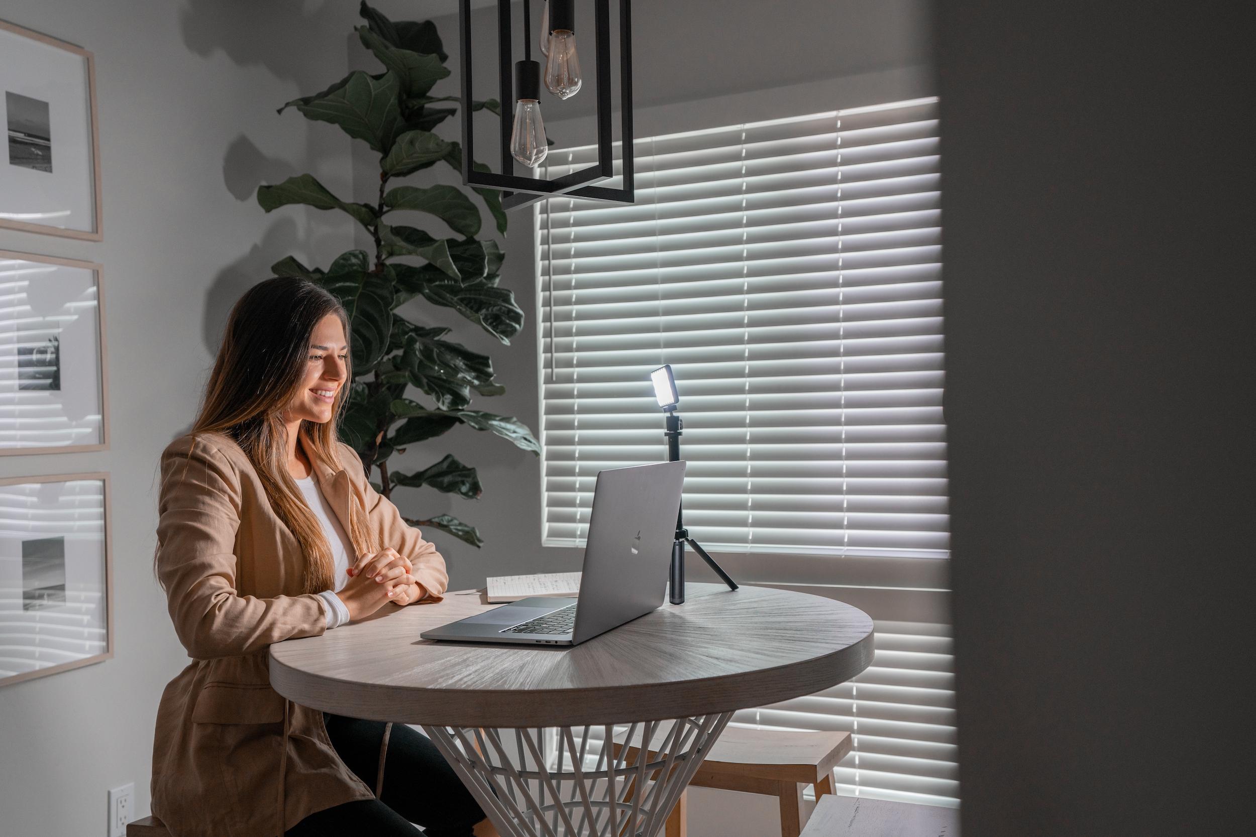 girl smiling sitting in home office using broadcast lighting kit