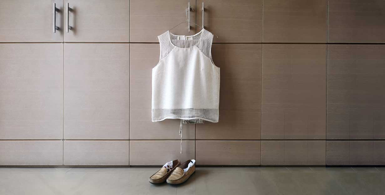 Woman's shirt hanging on closet and shoes