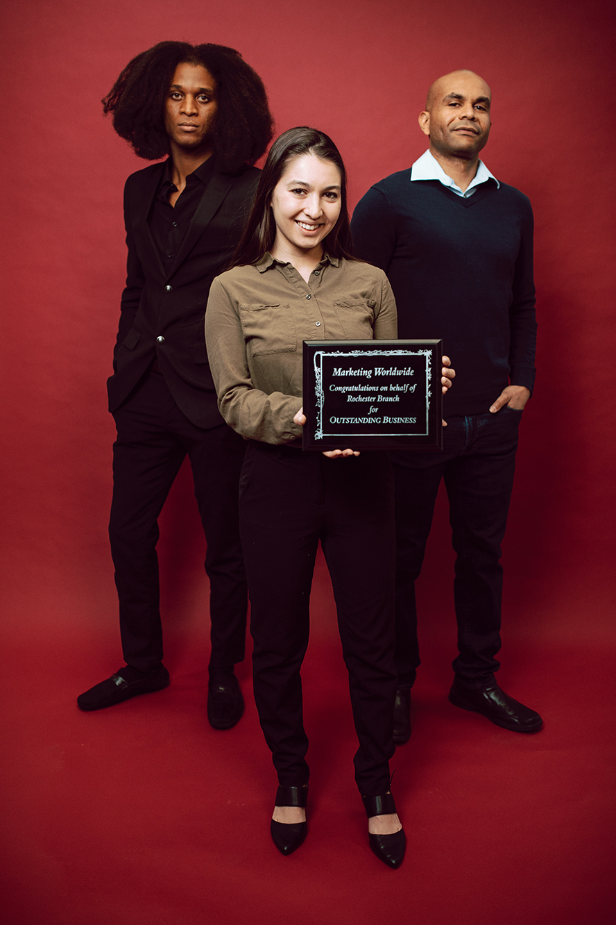 Employees showing off an award.