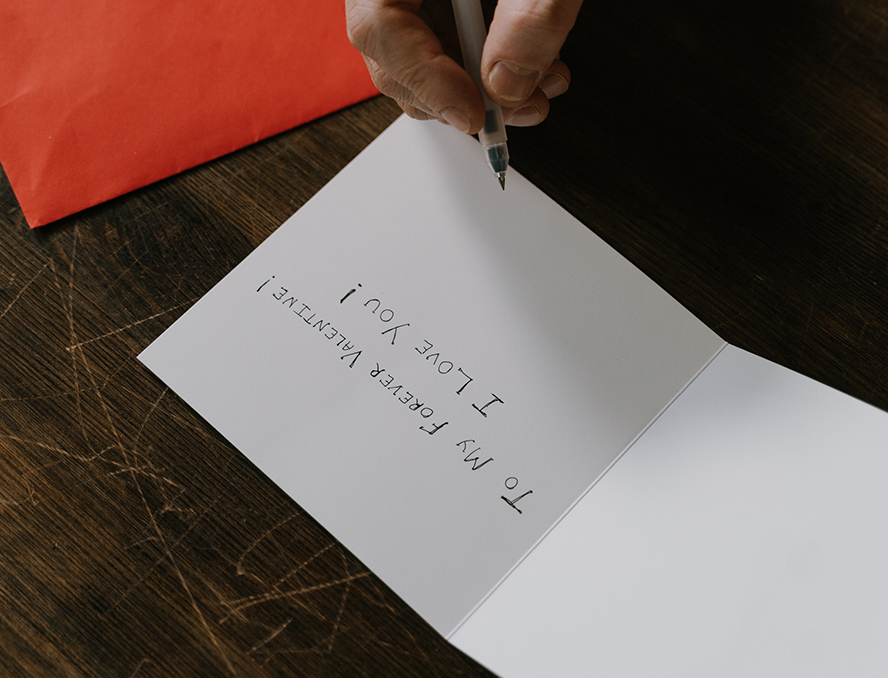 """A person writing """"to my forever valentines, I love you!"""" in a card."""