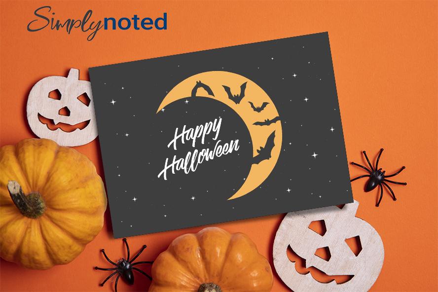 A happy Halloween card set against pumpkins on an orange table.