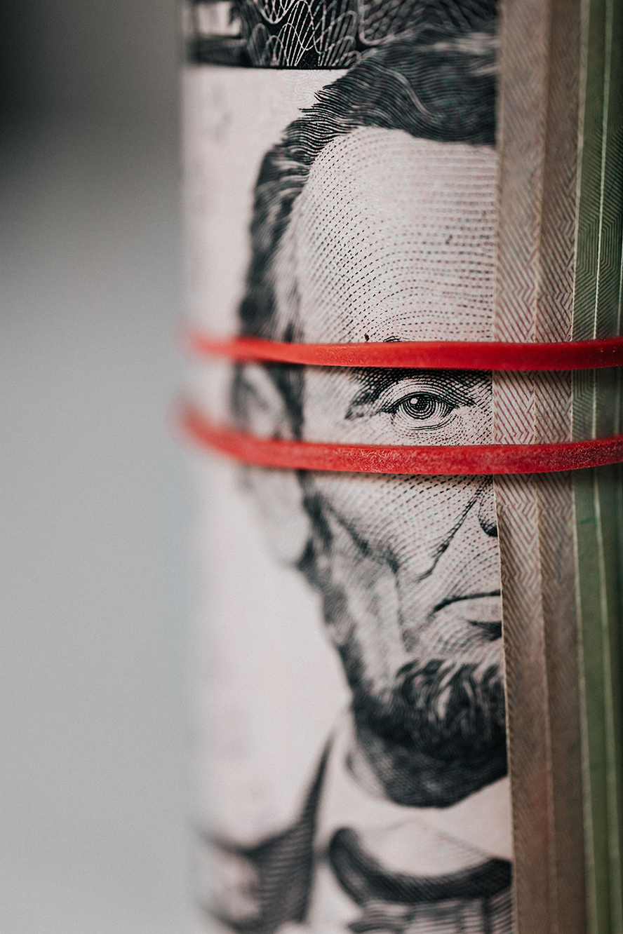 Close up of a roll of five dollar bills.