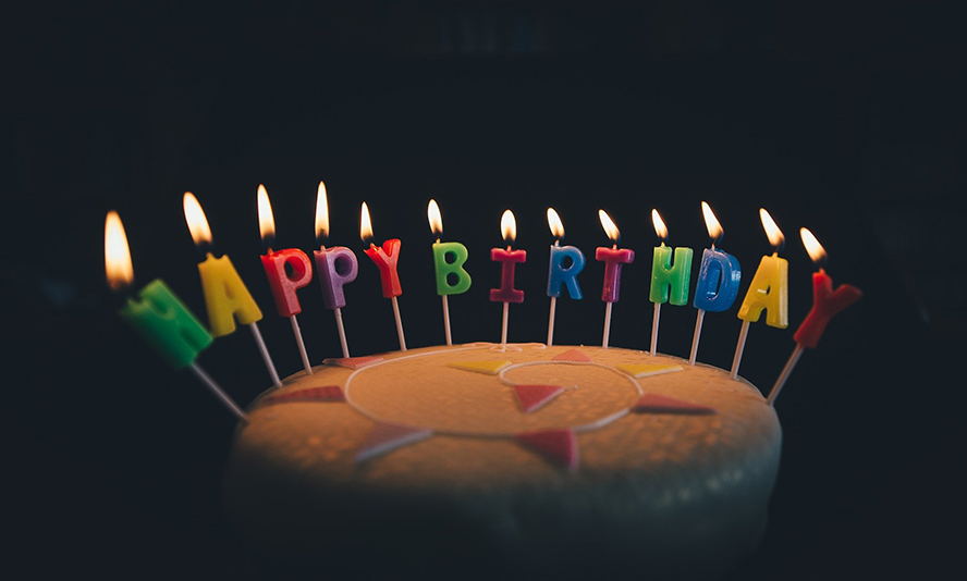 """A birthday cake in a darkened room with lit candles shaped like letters that spell """"happy birthday."""""""