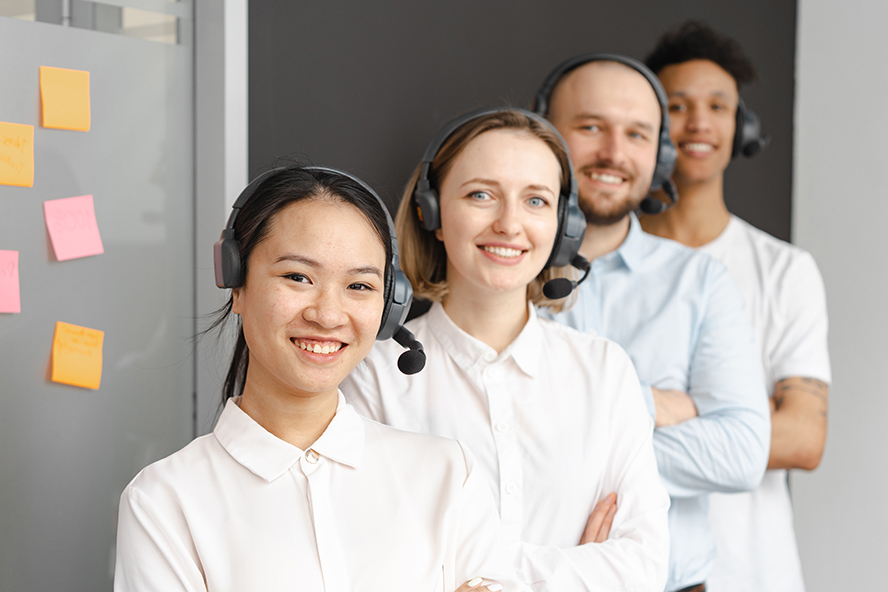 A sales team posing with their headsets on.
