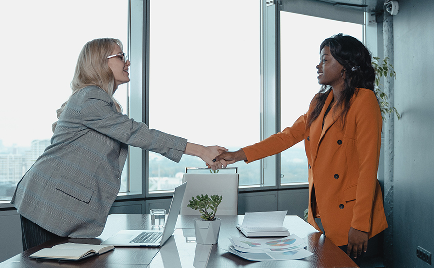 Two women shaking hands.