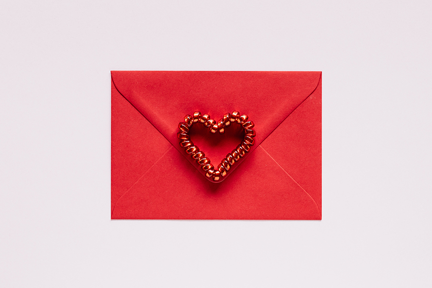 A red envelope with a decorative heart on it.