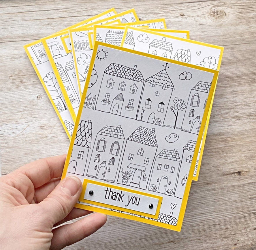 A stack of thank you cards with hand-drawn houses on them.