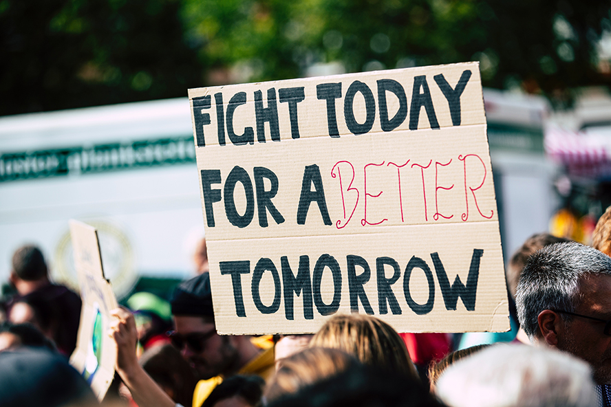 """Protestor holding up a sign that says """"Fight today for a better tomorrow."""""""