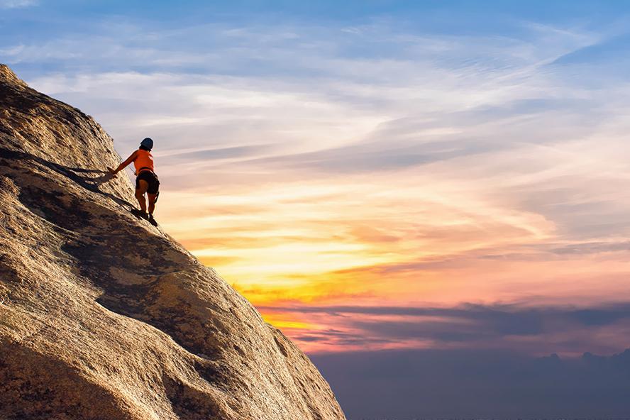 An inspiring image of a woman climbing a mountain.
