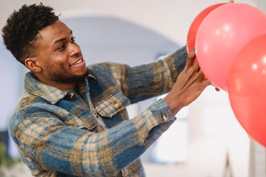 Guy helping hang balloons at a party.