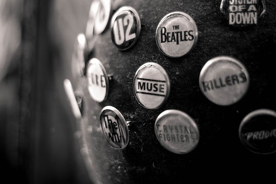 An assortment of band logos on pins.