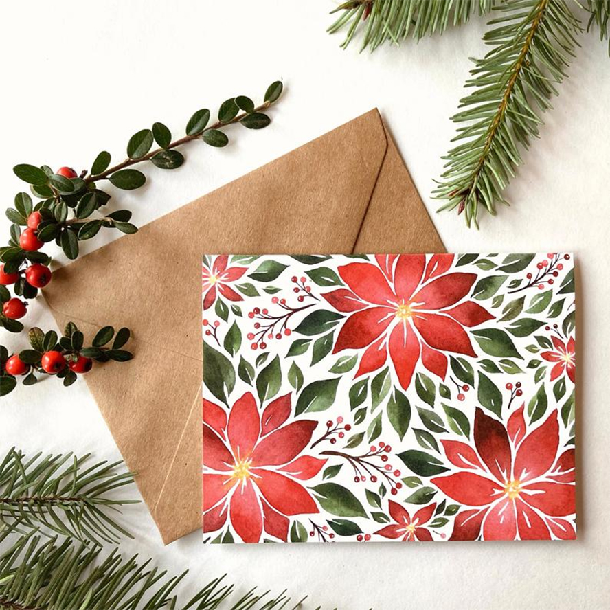 A holiday card with red flowers printing on it