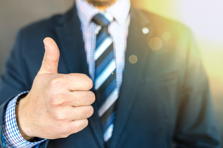 A close up of a man in a suit giving a thumbs up.
