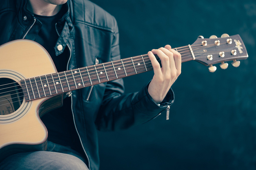 Close up of a guitar player wearing a leather jacket.