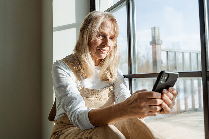 An older woman making an emotional connection with her phone.