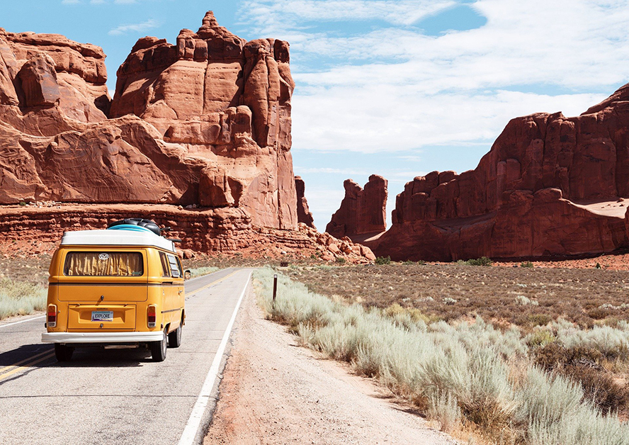 A VW van trekking out on a road trip across the desert.