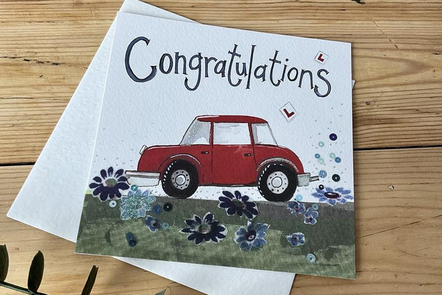 """A greeting card with an illustrated red car and the word """"Congratulations"""""""