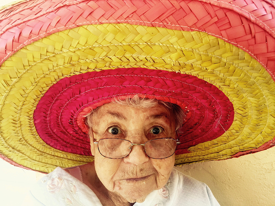 An older woman wearing a brightly-colored sombrero.