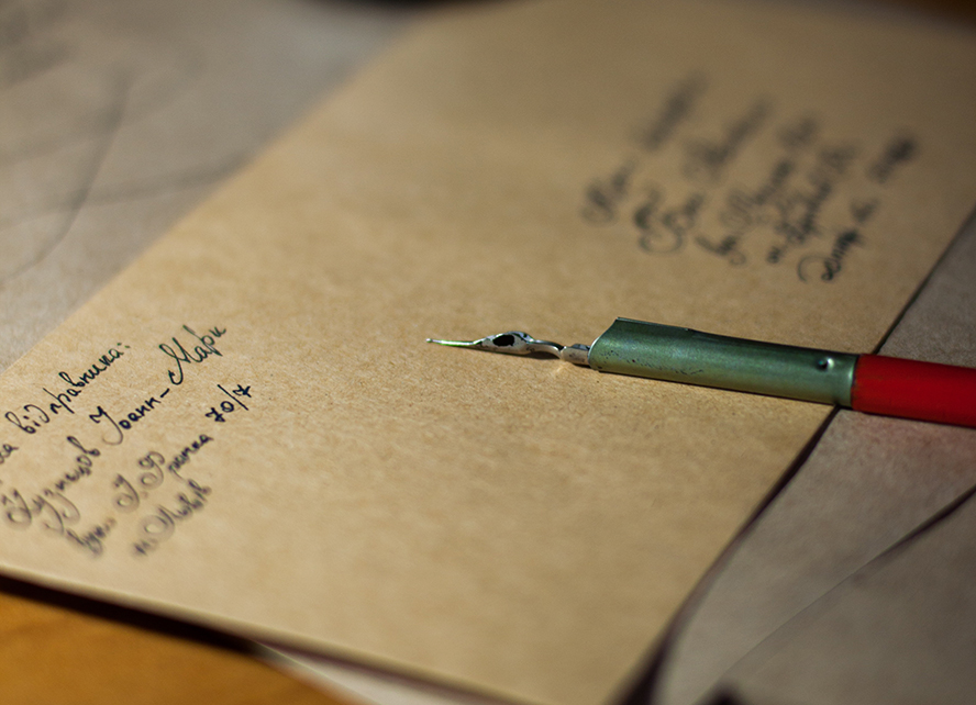 Close up on a pen sitting across a hand-addressed envelope.