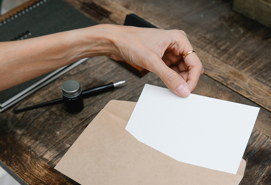 A woman pulling a letter out of an envelope.