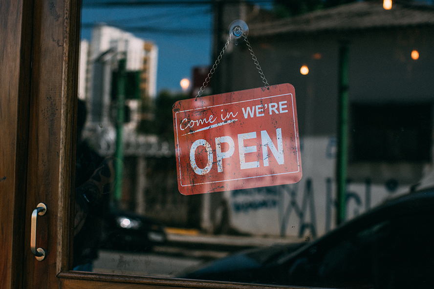 """Close up on a business's door displaying at """"Come in we're open"""" sign."""