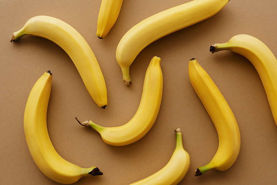 Bananas scattered out over a brown table.