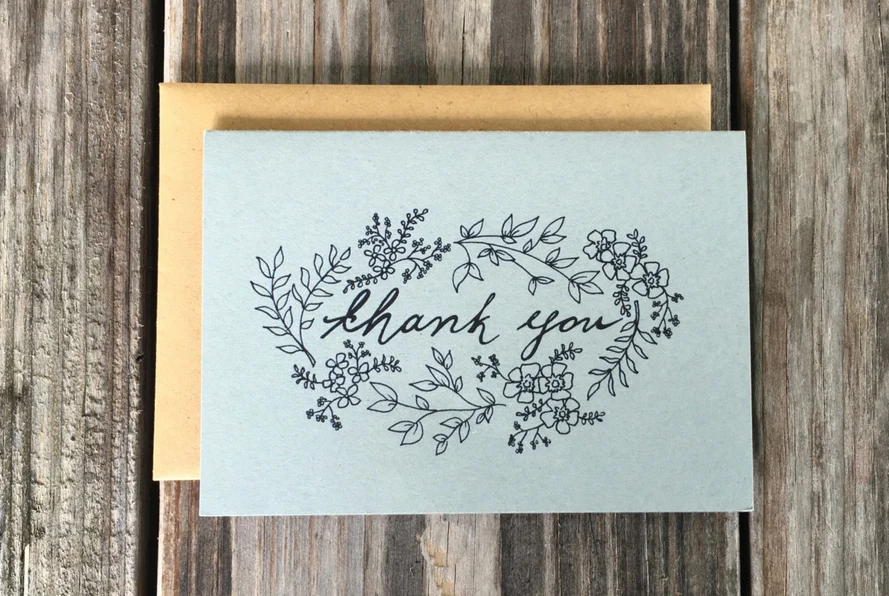 A lovely thank you card on a wood table.