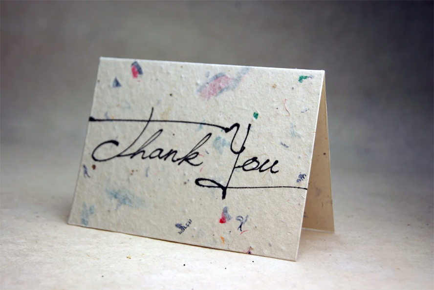 A thank you card standing up against a neutral background.