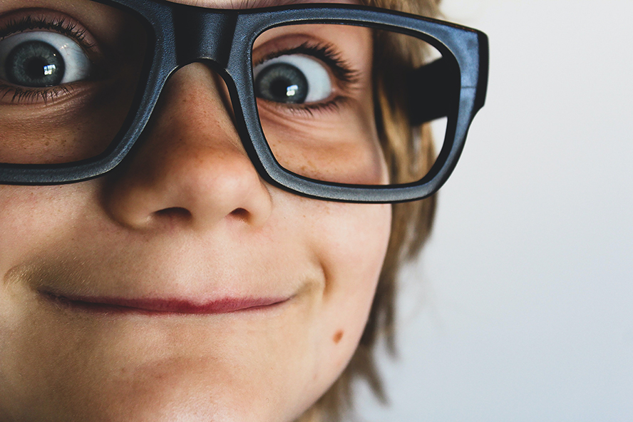Close up of a kid with glasses smiling funny at the camera.
