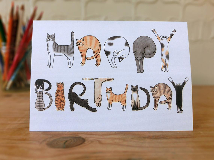 """A birthday card that spells """"Happy Birthday"""" with illustrated cats."""