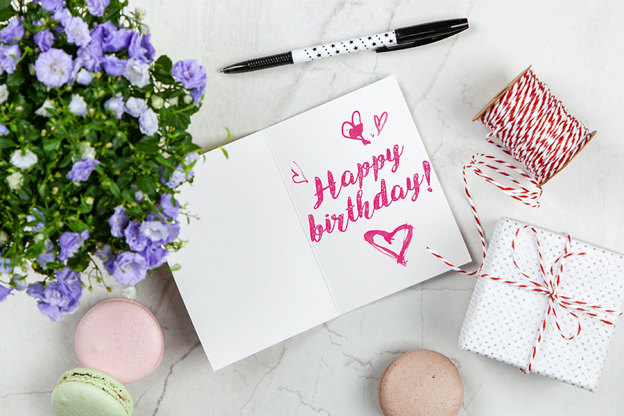 A birthday card with flowers to its right.