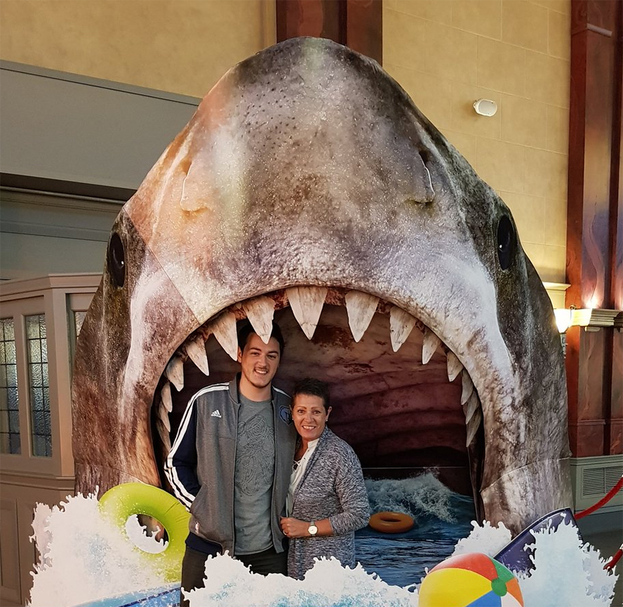 A pair of people posing and laughing in front of a giant cardboard shark standee.