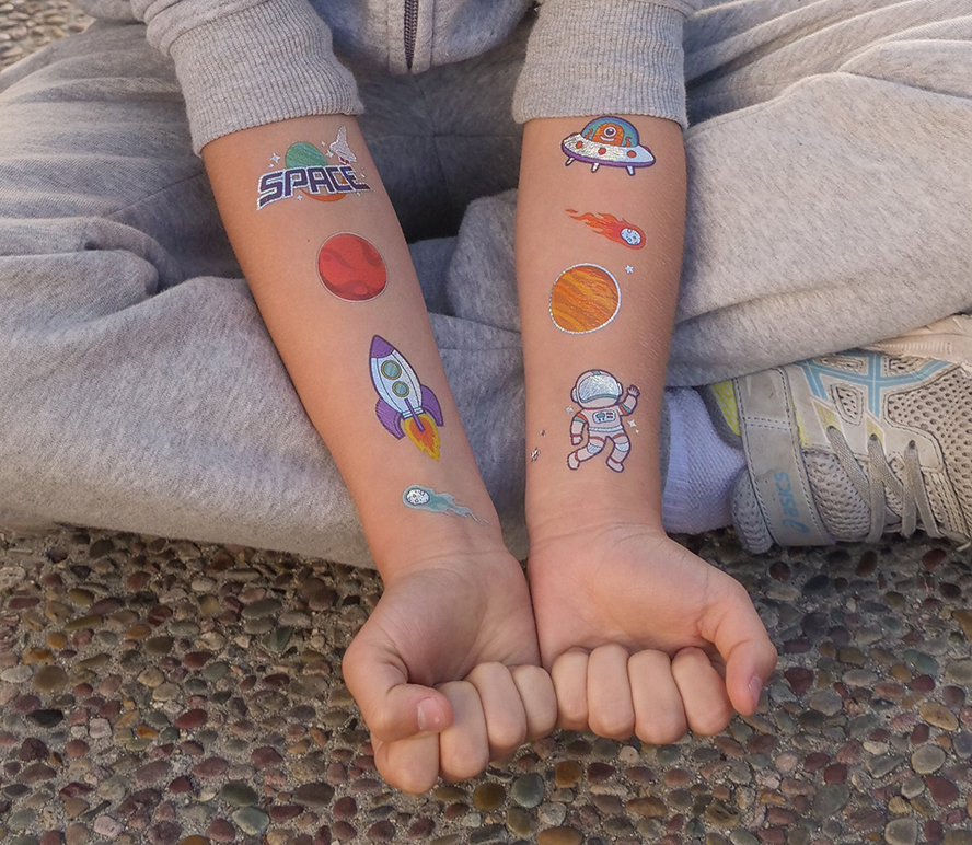 Close up of a kid's arms with temporary tattoos.