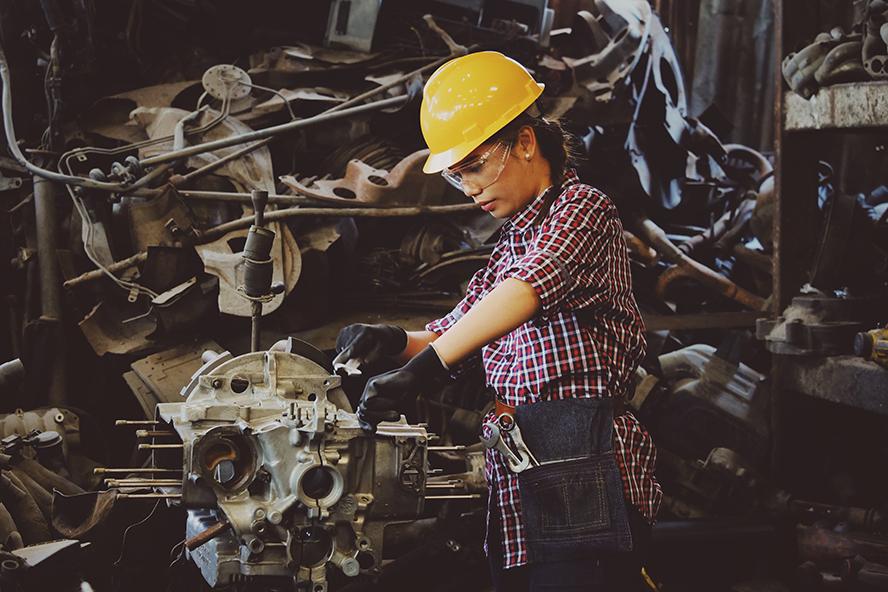 Skilled female auto mechanic working on an engine