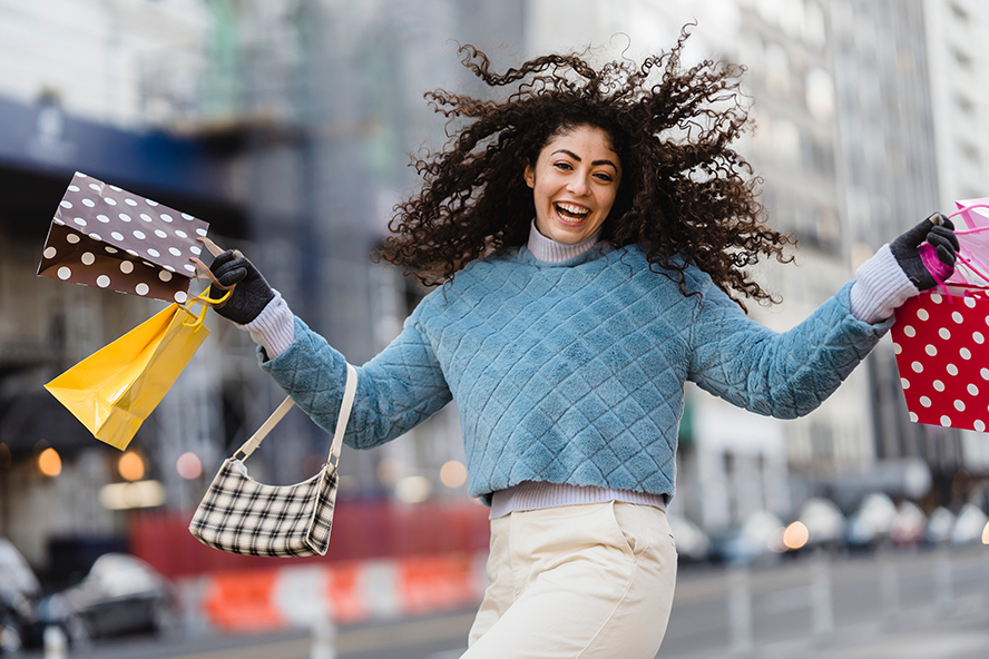 A woman smiling broadly with a bunch of shopping bags in hand.
