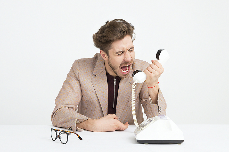 An angry customer yelling into the phone. Image has comedic overtones.