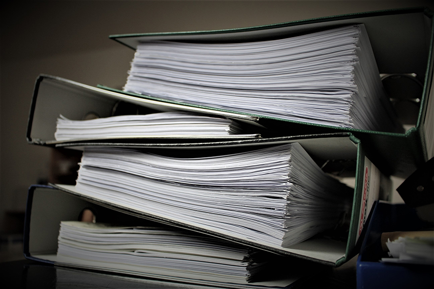 Stacked binders stuffed full with documents.