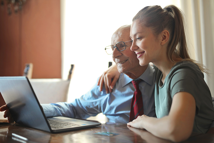 Woman helping an older man with his computer