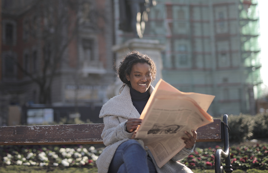 A woman on a park bench reading a newspaper.