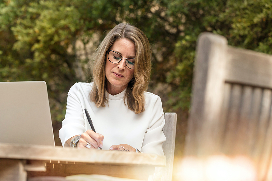 A woman writing on a table outside.