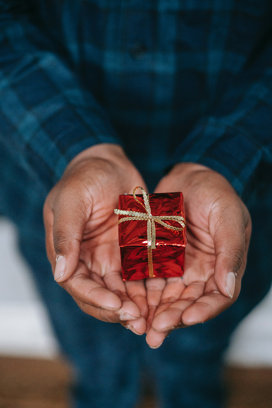 A women holding out a small wrapped gift.