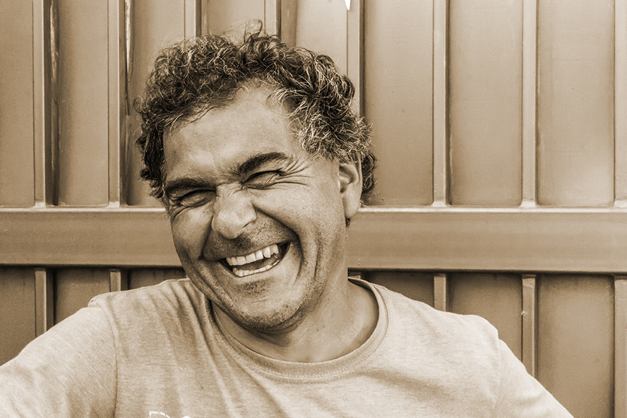 Older guy laughing to himself. Sepia tone image.
