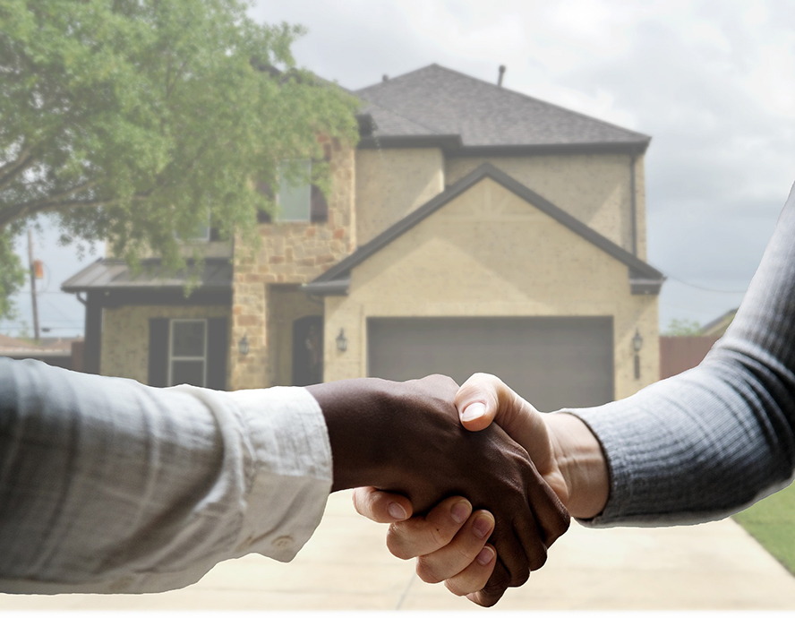 Two men shaking hands in front of a home.