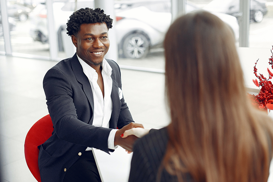 Man buying a car and shaking hands with the saleswoman.