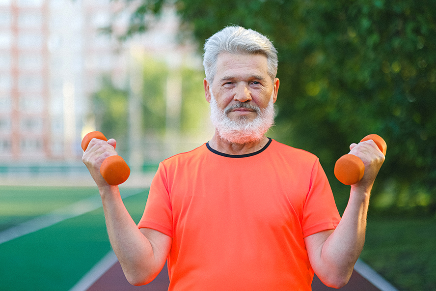A healthy older man, lifting light weights.