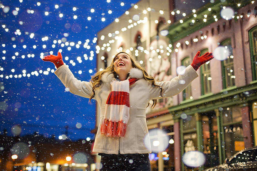 A woman standing outside at Christmas time smiling in the snow.