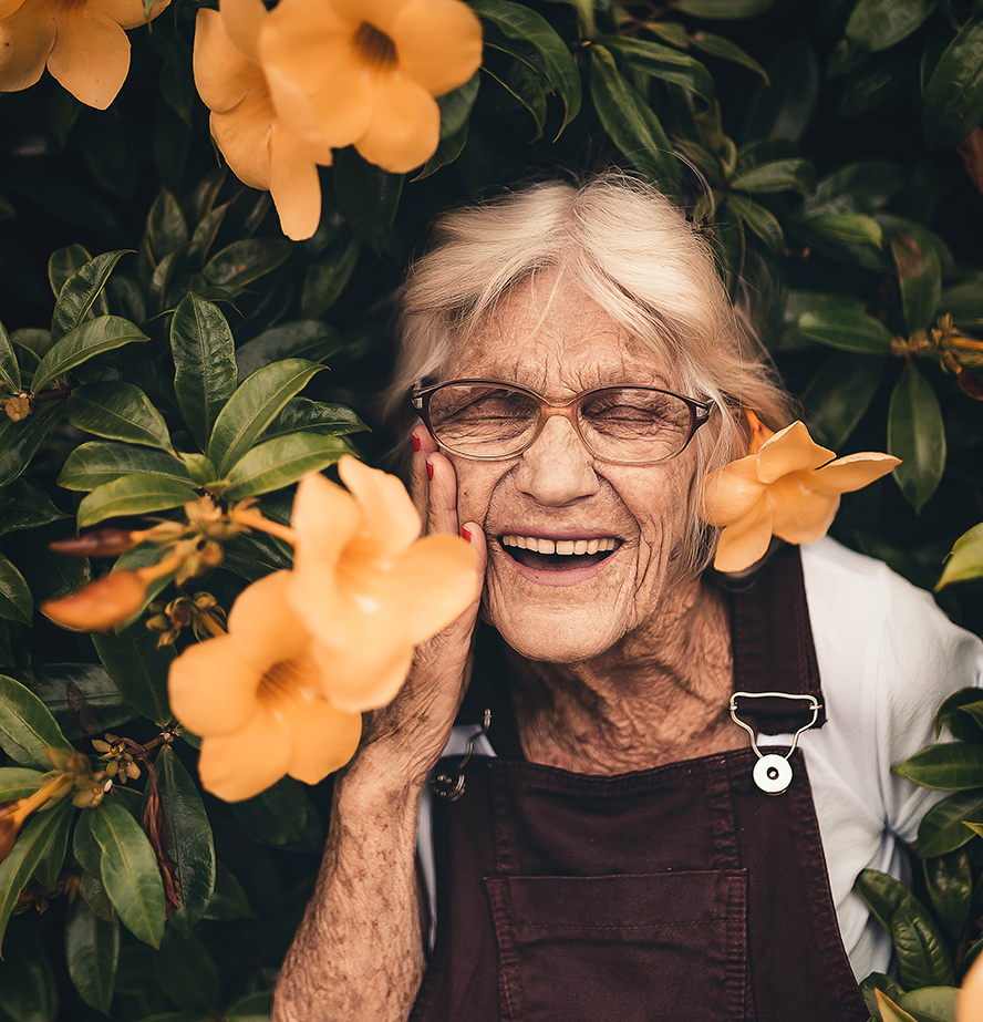 An older woman posing with flowers