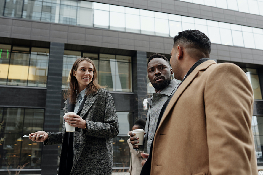 A group of three business people talking on a city street.