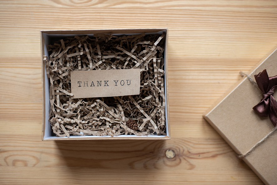 """A gift box opened to reveal a note that says """"Thank You""""."""
