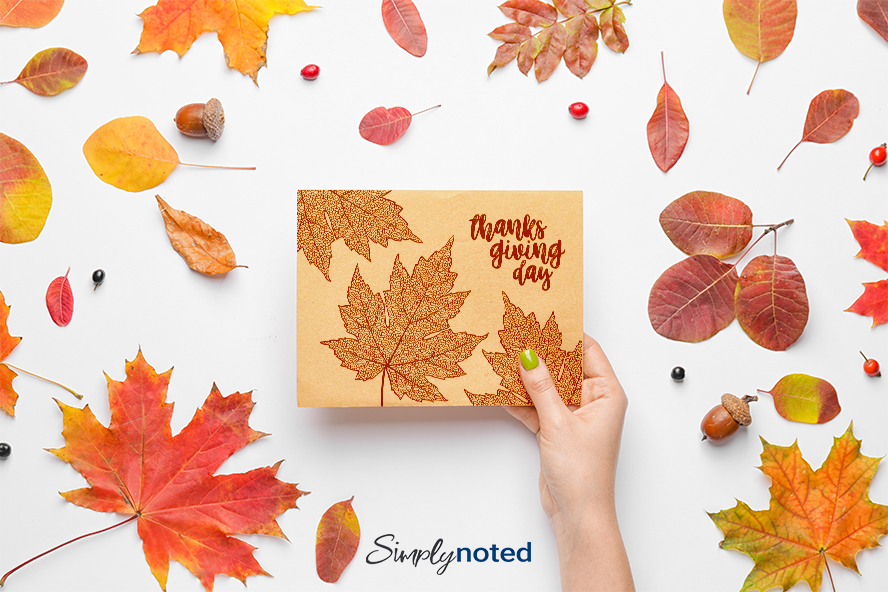 A woman holding a Thanksgiving card against a backdrop of acorns and leaves.
